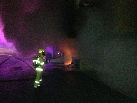 Firefighter battles the car fire in Jerilderie Court
